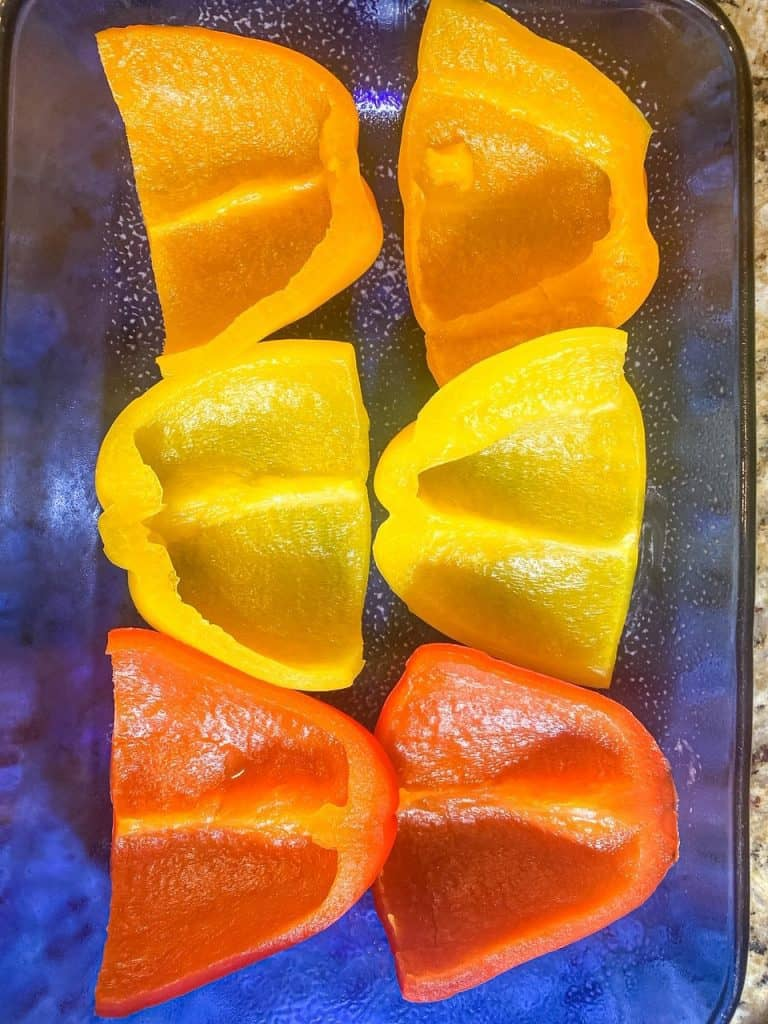 hollow peppers cut in half in baking dish for Cheesy Taco Stuffed Peppers with Beef
