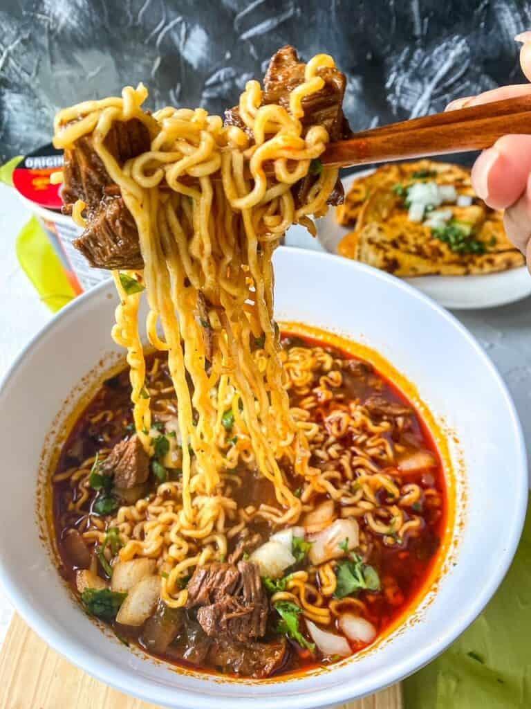 noodle pull of birria ramen wiht beef