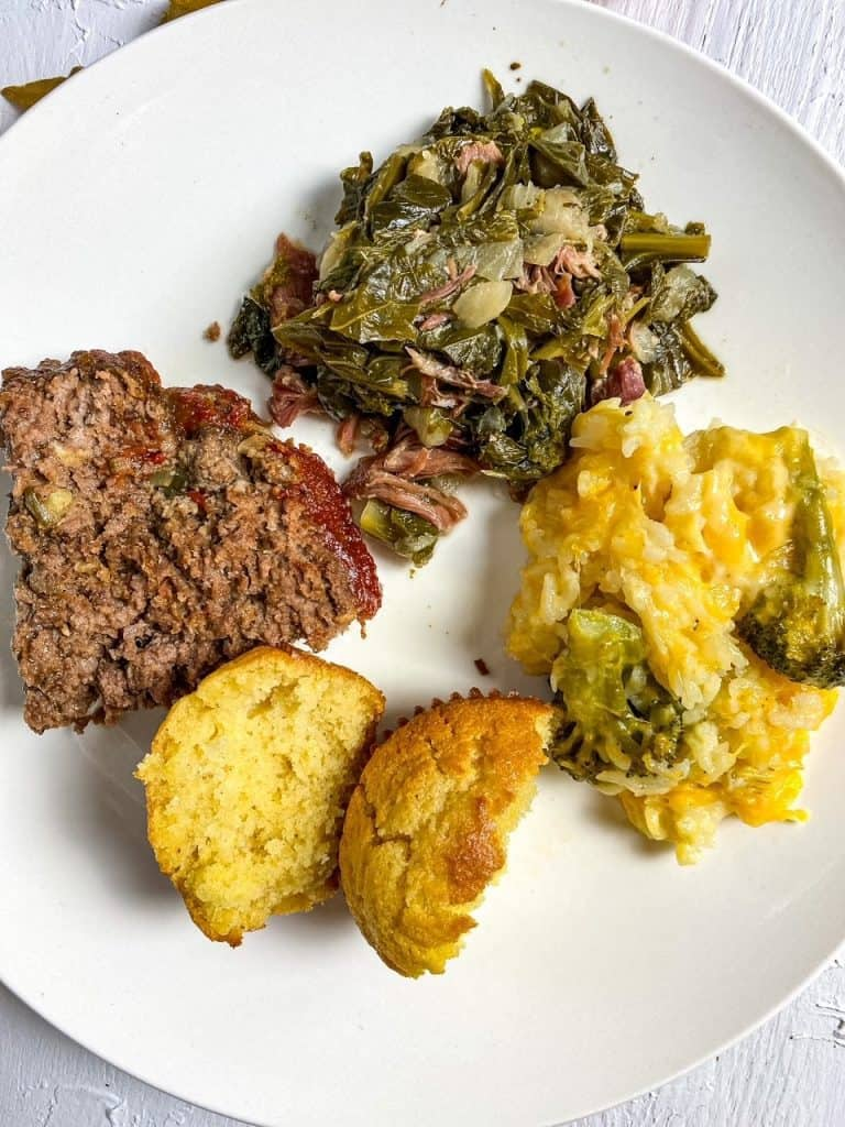 plated NaNa's Juicy Homestyle Meatloaf with a Special Ingredient with sides of greens, cornbread, and broccoli