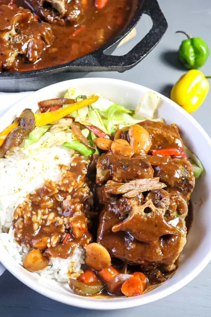 oxtails plated in a bowl with rice and cabbage
