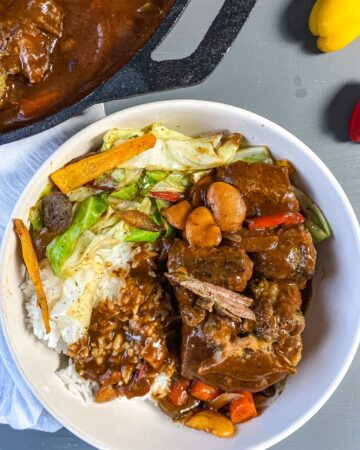 overhead view of plated oxtails in a bowl