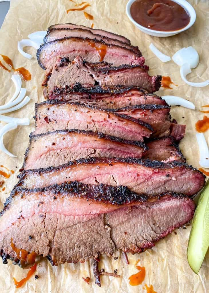 sliced up front angle of bbq beef brisket with onions and pickles