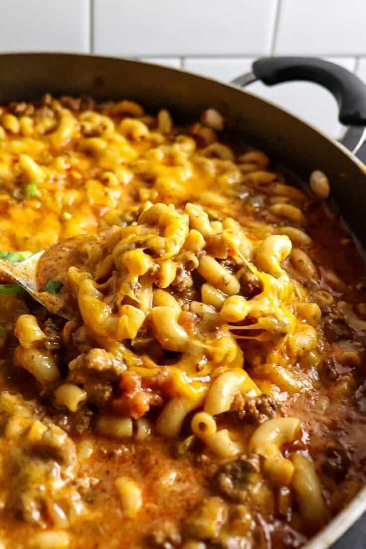 A big spoonful of Chili Mac and Cheese with a heaping pot of more behind it