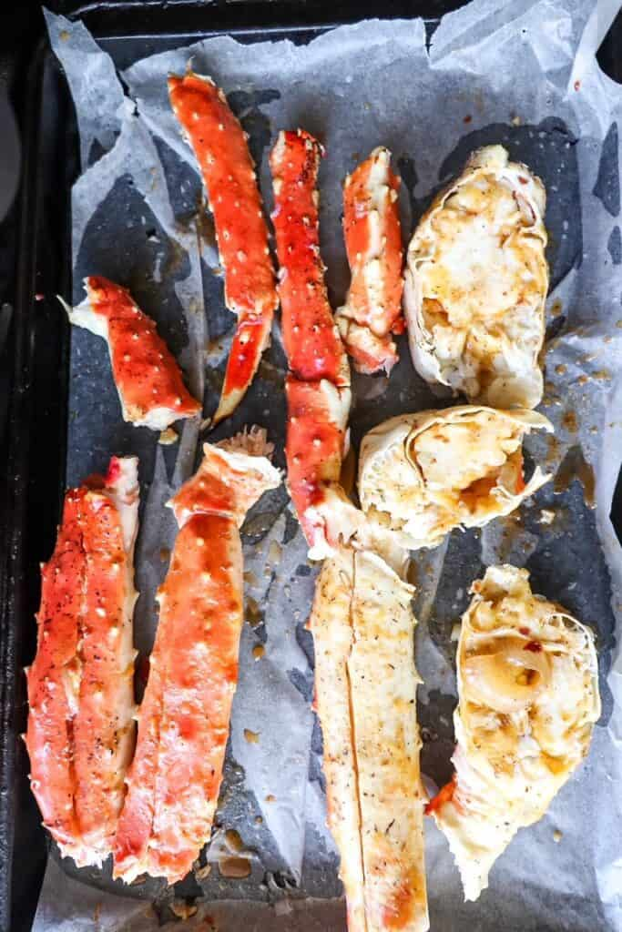 split king crab legs sitting on a baking dish lined with parchment paper