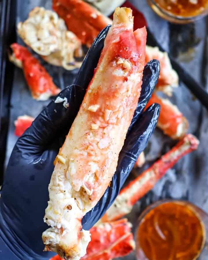a piece of deshelled king crab held in the palm of a hand to show how large it is