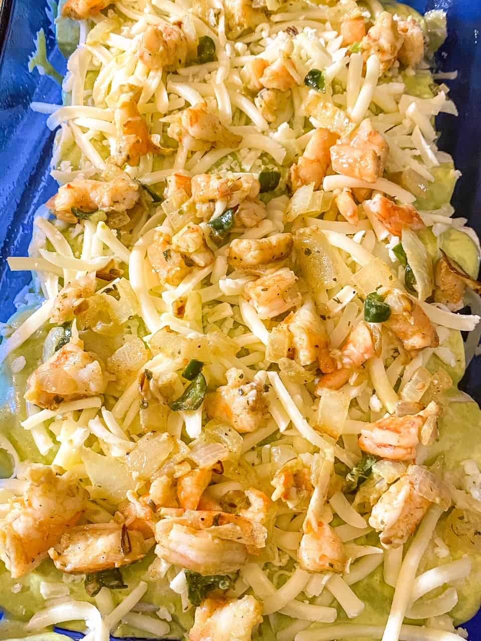 shrimp enchiladas prepared in a dish before they are baked