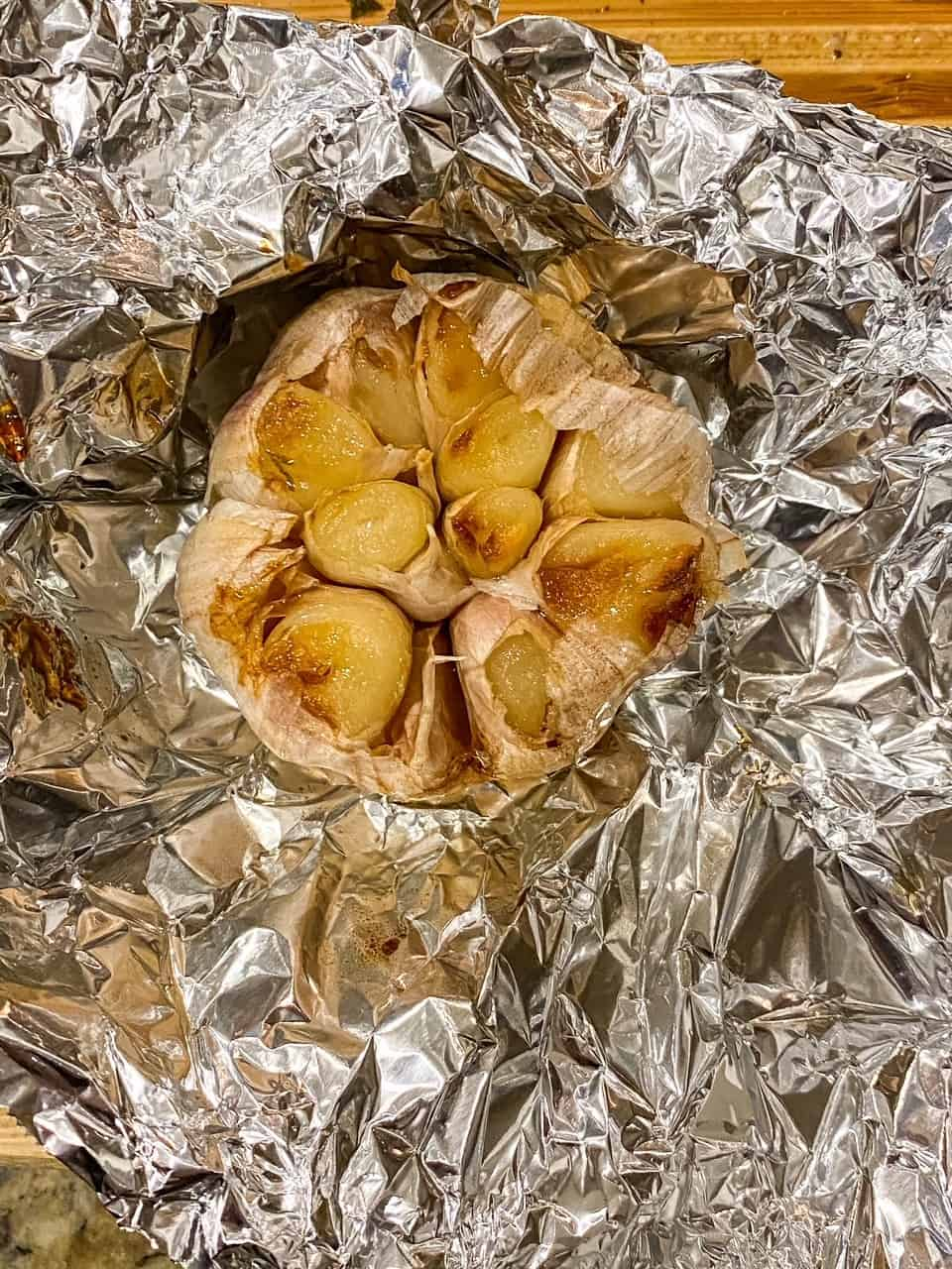 roasted garlic sitting on aluminum foil to be added to the blender for the creamy poblano sauce