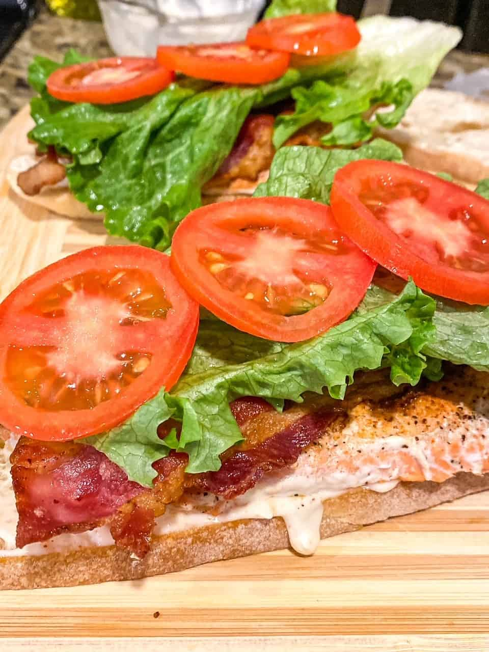 piece of bread with salmon, bacon, lettuce, and tomato on it to make a salmon BLT