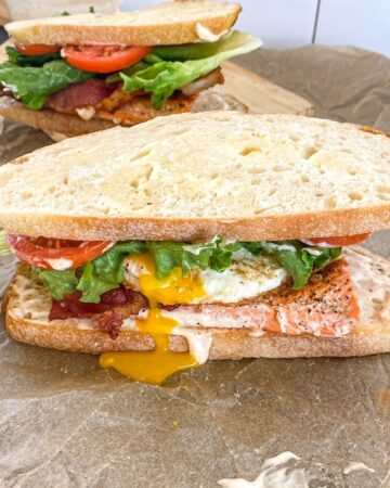 blackened salmon BLT sandwich on a cutting board with egg yolk dripping out