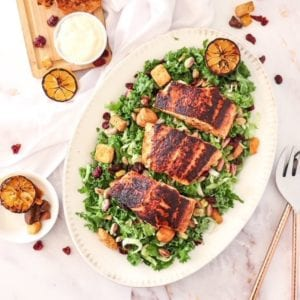 overhead of kale salad with blackened salmon on a platter