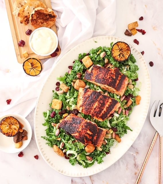 photo of kale salad on a platter with blackened salmon