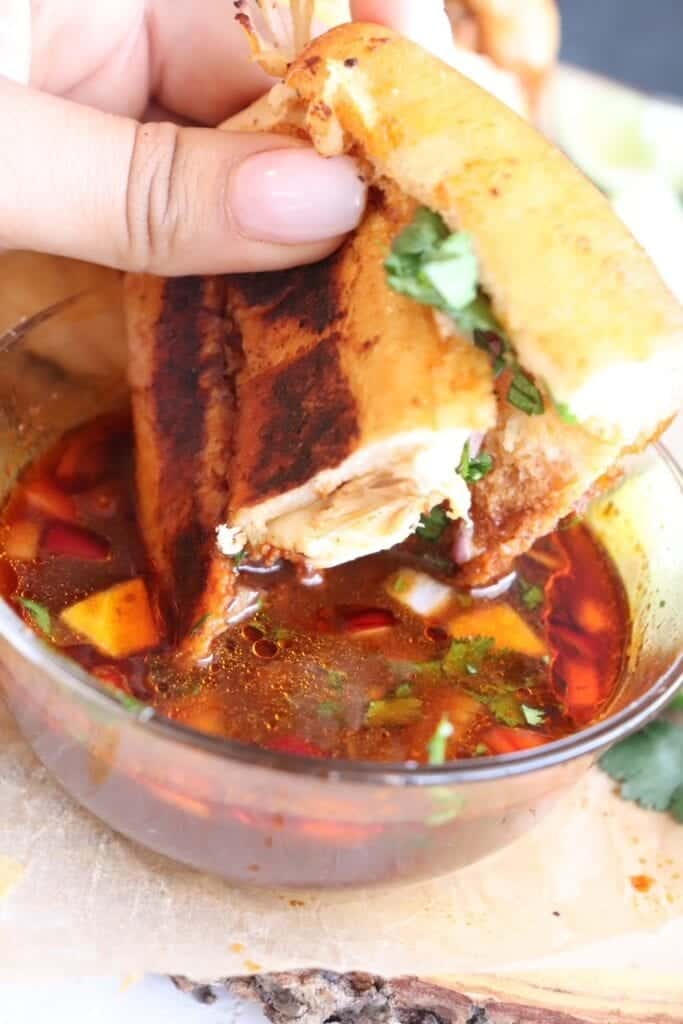 dipping chicken birria grilled cheese sandwiches into the consome sauce