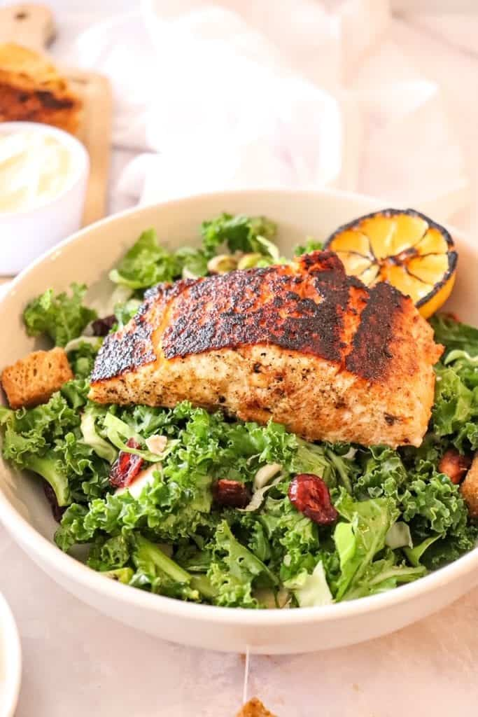 photo of kale salad in a bowl with blackened salmon